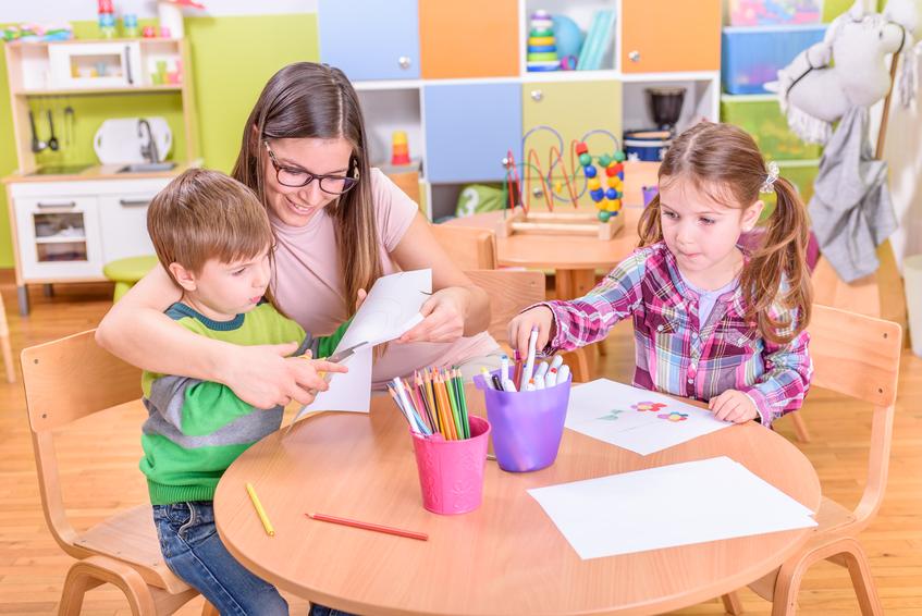 two kids with a teacher in a kindergarten class