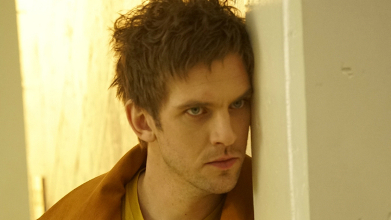 Dan Stevens as David Haller leans against a white wall looking angry in Legion
