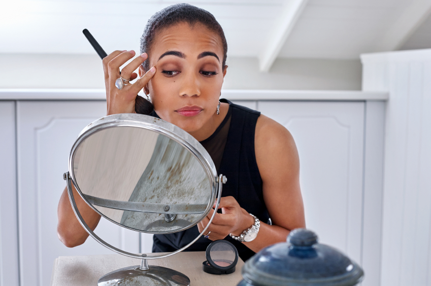 woman doing makeup in front of a mirror
