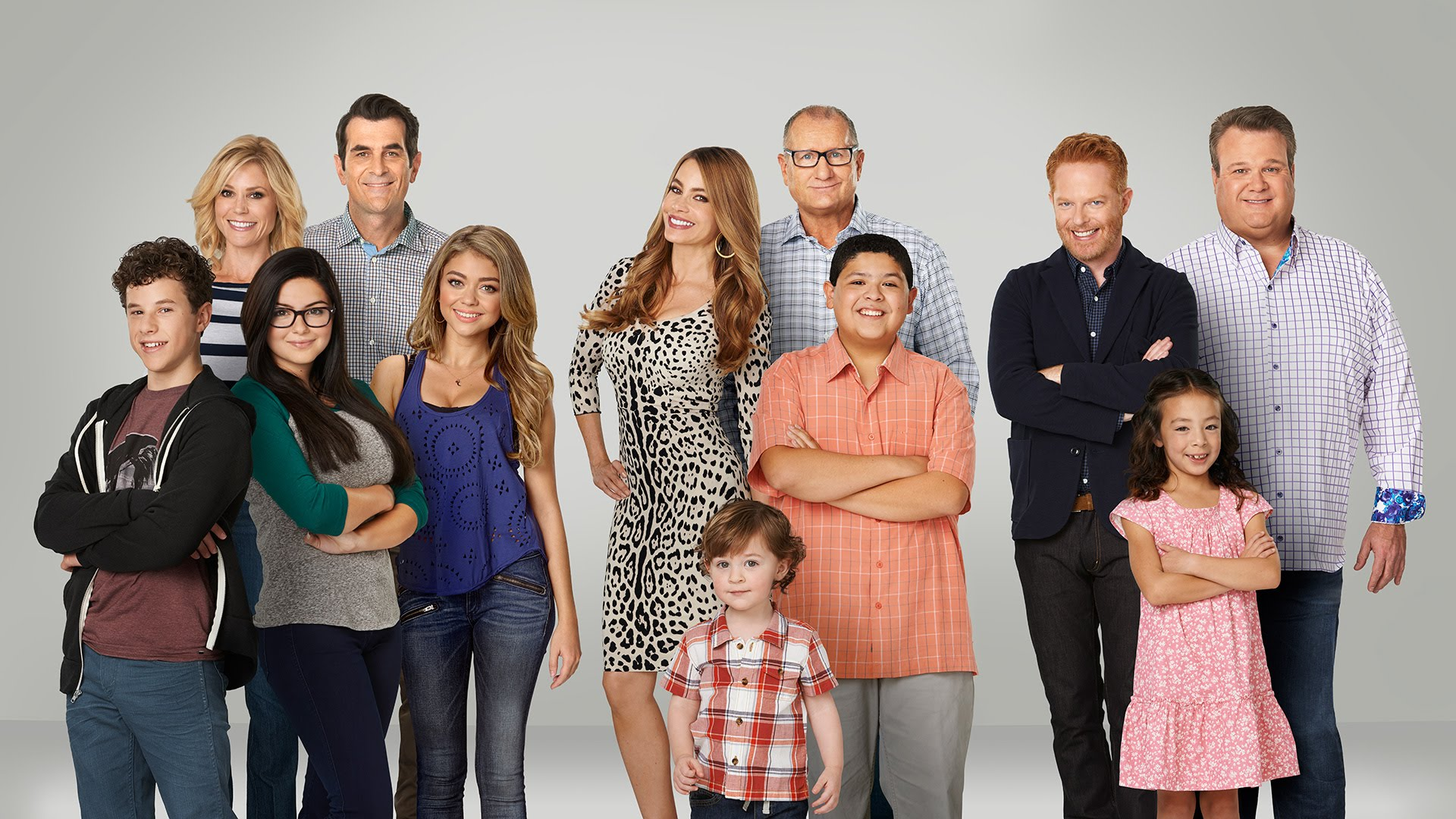 The cast of Modern Family stand in front of a white background