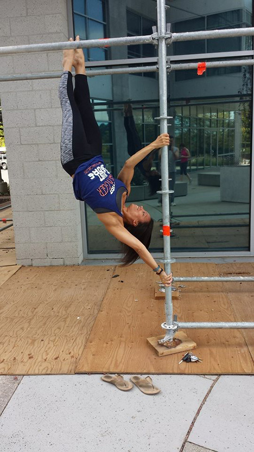 Michelle Abbruzzese performing pole tricks on some scaffolding