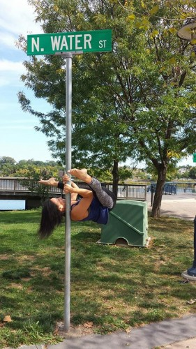 Michelle Abbruzzese performing a pole dancing trick on a street sign