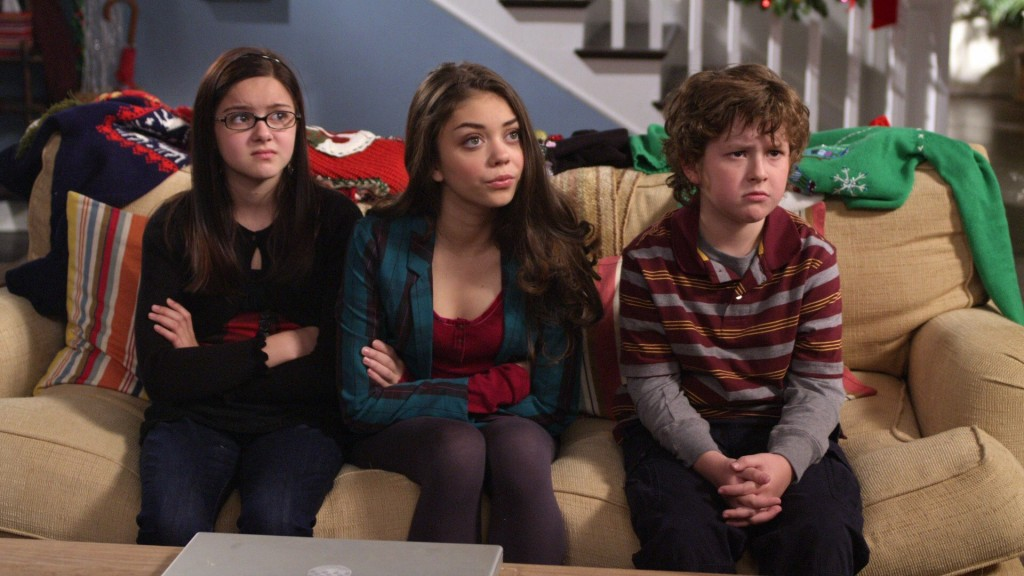 Sarah Hyland, Ariel Winter,and Nolan Gould sit on a couch and stare ahead in Modern Family