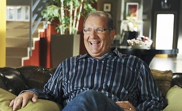 Ed O'Neill sits on a couch in Modern Family