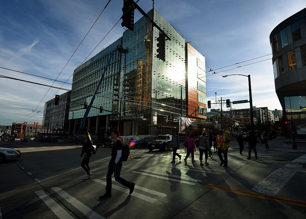 People walk past part of the new Amazon headquarter complex under construction in downtown Seattle, Washington