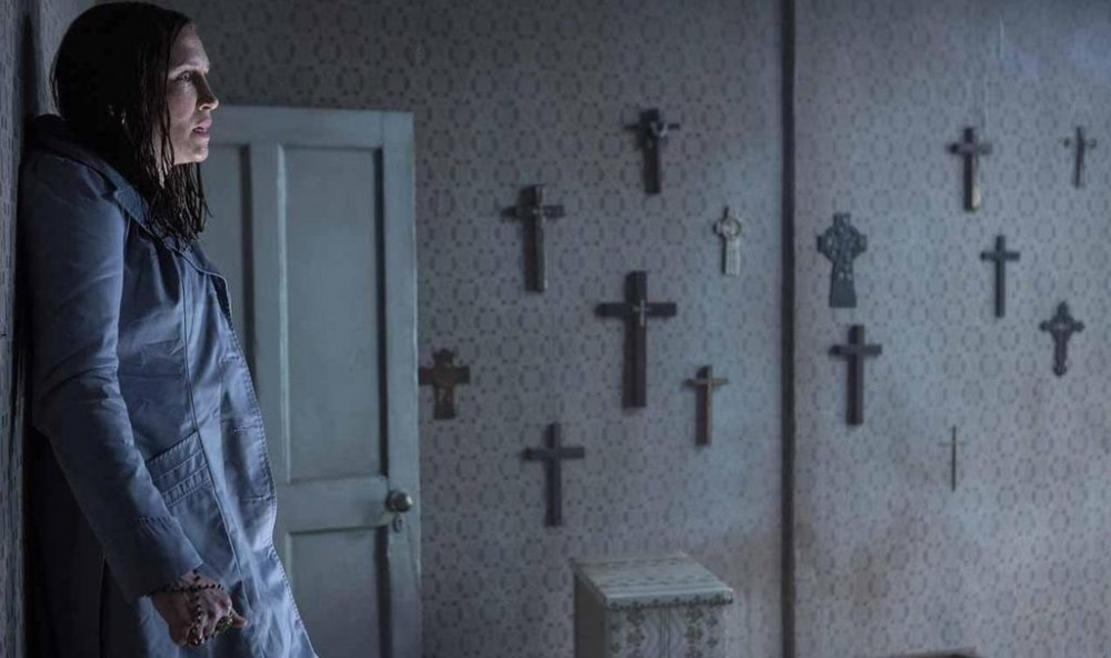 Vera Farmiga up against a wall, in a room covered in crucifixes