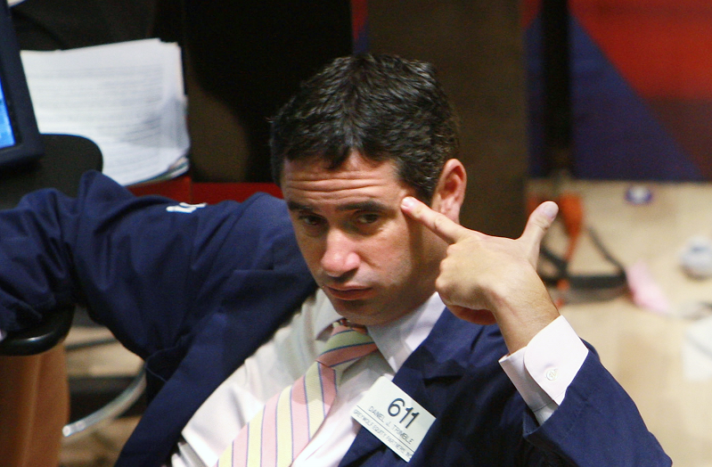 A stock trader puts his finger to his head as the realization of the 2008 financial crisis, spurred by the meltdown of toxic subprime mortgages, took hold