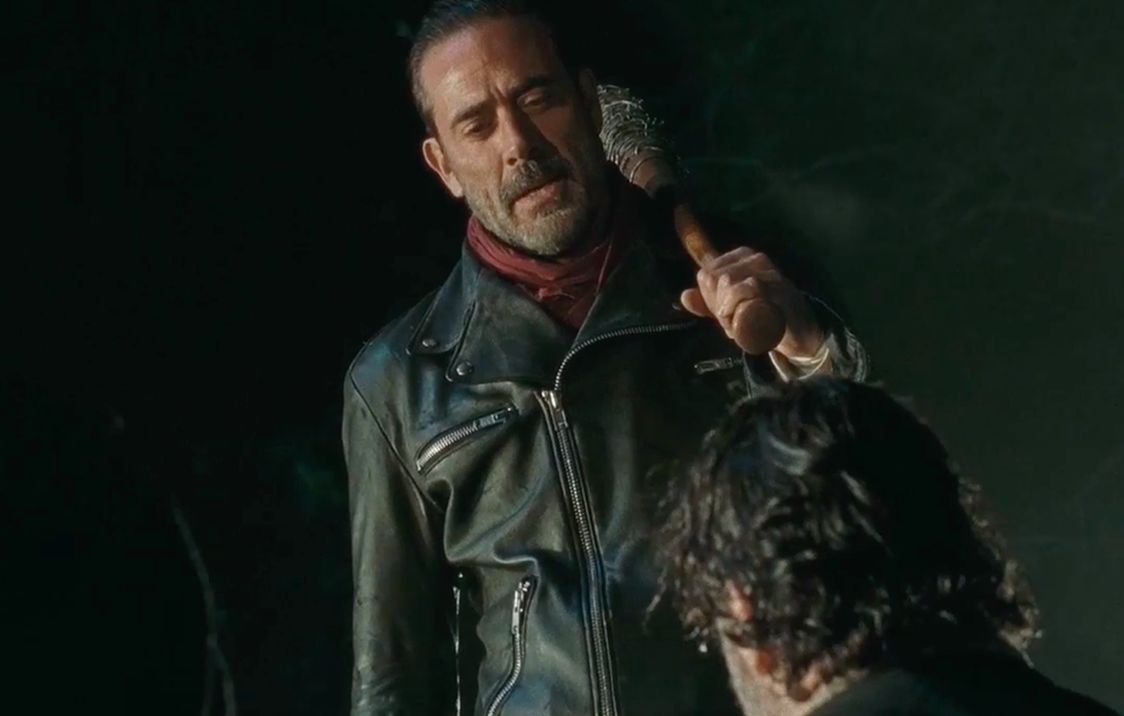 Negan wearing a black leather jacket and red scarf, holding a baseball bat over his shoulder and looking down on a kneeling Rick Grimes