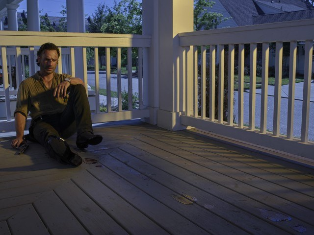 Rick Grimes (Andrew Lincoln) sits alone on a porch in a scene from the sixth season of 'The Walking Dead'