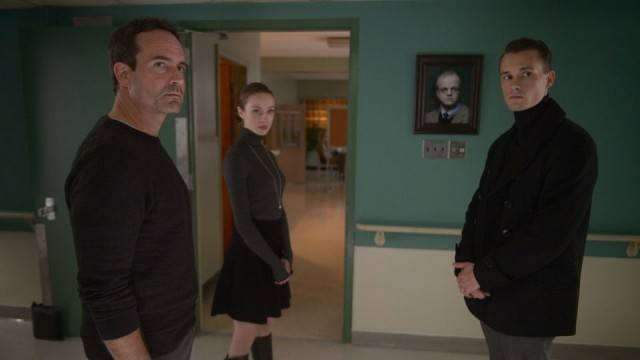 Two men and a woman in a hallway.