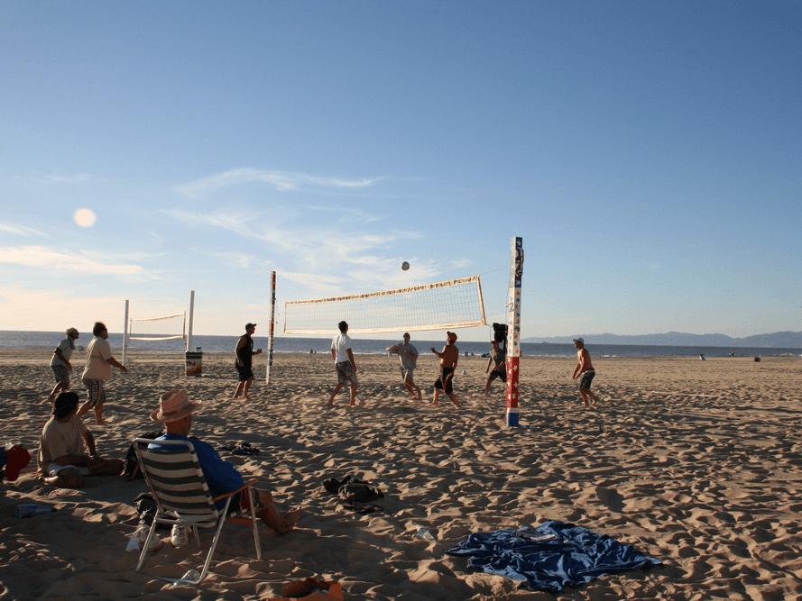 Beachgoers play volleyball on a California beach