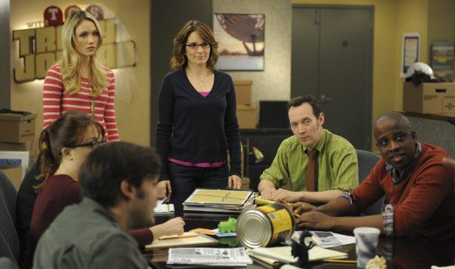 Liz, Jenna and other characters standing in front of a table filled with other characters.