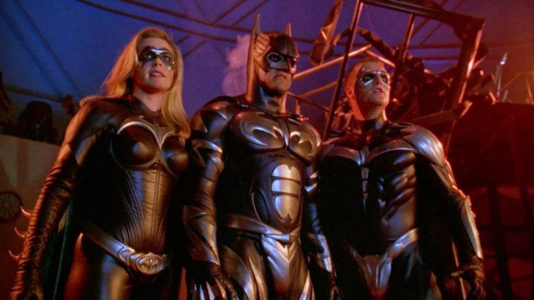 the cast of Batman and Robin stand in their bat suits