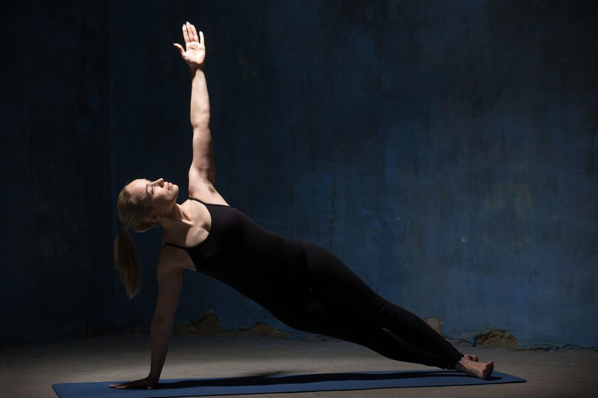 woman doing a side plank on a yoga mat