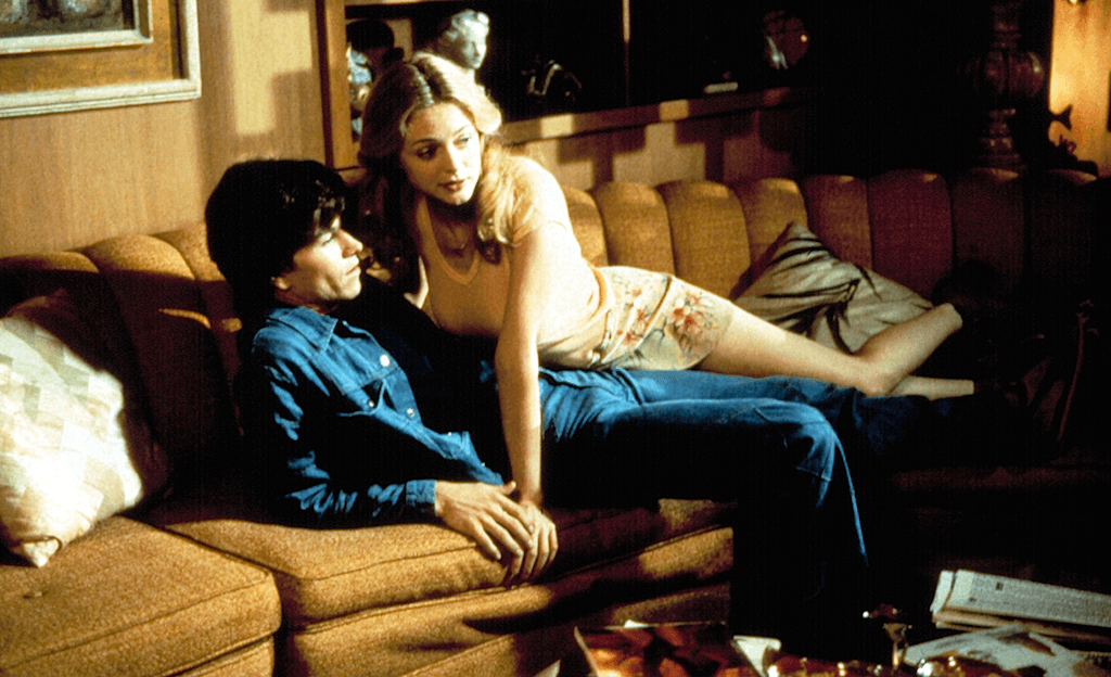 Dirk Diggler with Rollergirl on top of him on a couch