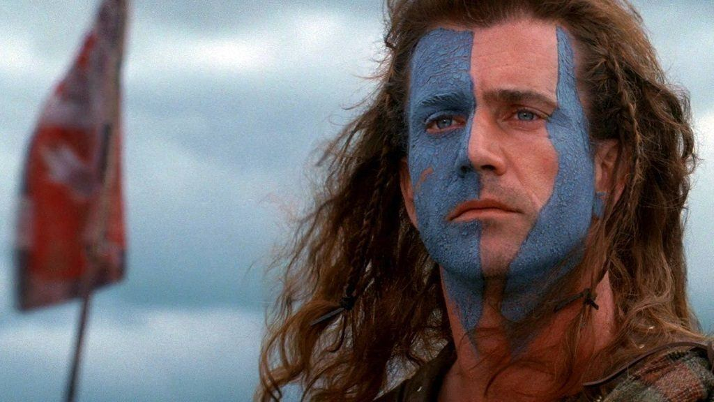 Mel Gibson with blue paint in parts of his face in front of a flag