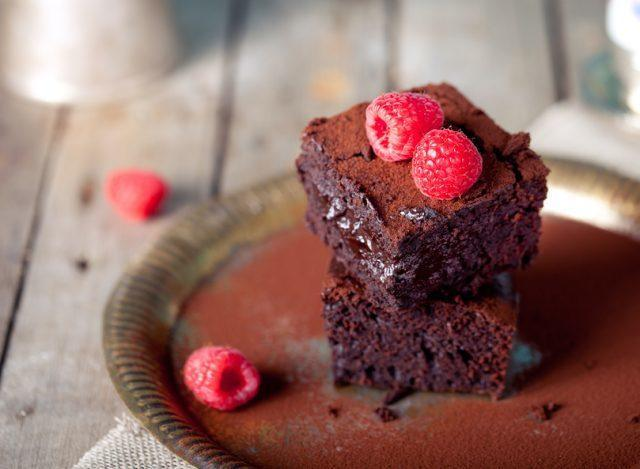 Brownies with fresh raspberries on a wooden background
