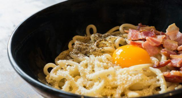 close-up of a bowl filled with noodles, bacon, and an egg