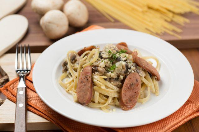 creamy mushroom and sausage pasta on a white plate