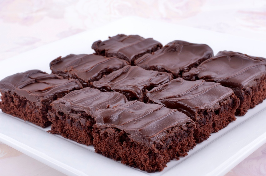frosted chocolate brownies on a white tray
