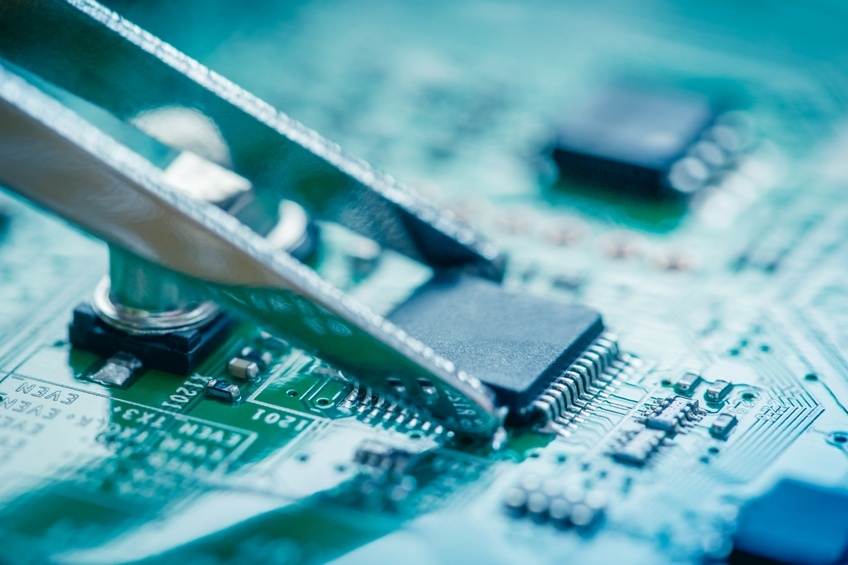 microchip catching with tweezers on circuit board.