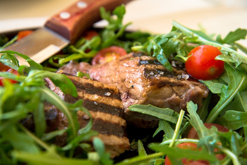 Close-up of a juicy steak served with an arugula and tomato salad