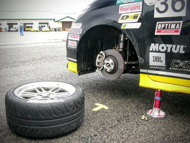 Racing wheels and brakes lay on the street during the 2016 One Lap of America Race