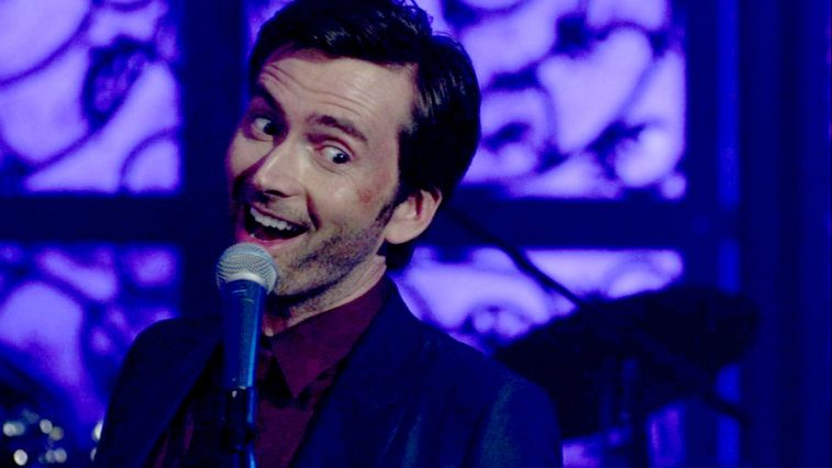 David Tennant as Kilgrave, smiling into a microphone against a purple background