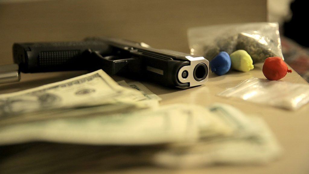 Money, guns and drugs lay on a table in a scene from Drugs, Inc.