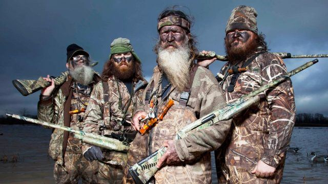 The cast of Duck Dynasty is posing together in camo and holding guns.