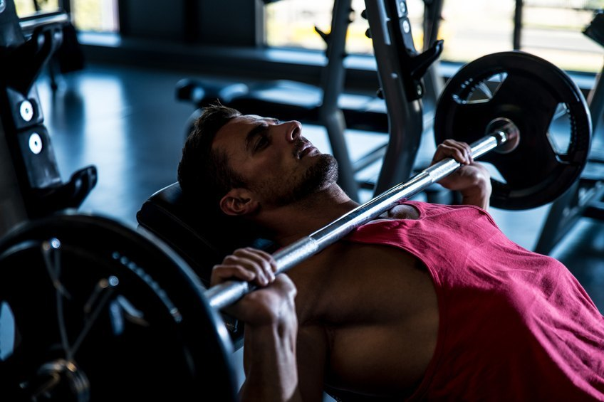 man doing bench press exercise on an incline bench