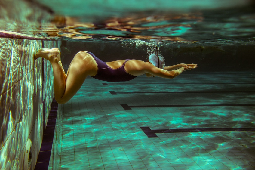 woman pushing off the wall in a pool