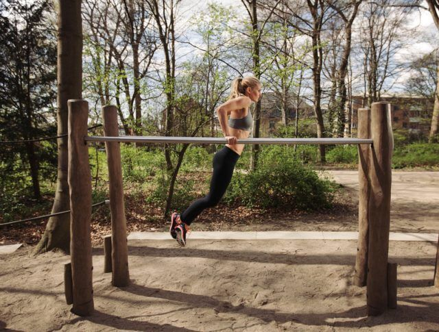 woman performing dips on a set of parallel bars at a park