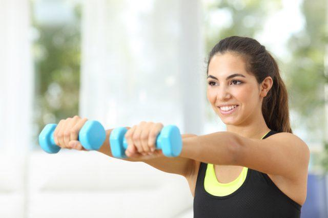 close-up of a woman's upper body as she exercises with dumbbells