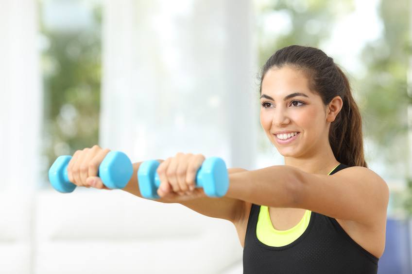 a woman doing dumbbell exercises at the gym