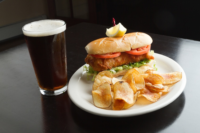 tilapia sandwich with chips and beer