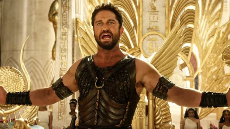 Gerard Butler holds his arms out while standing in front of a golden throne in Gods of Egypt