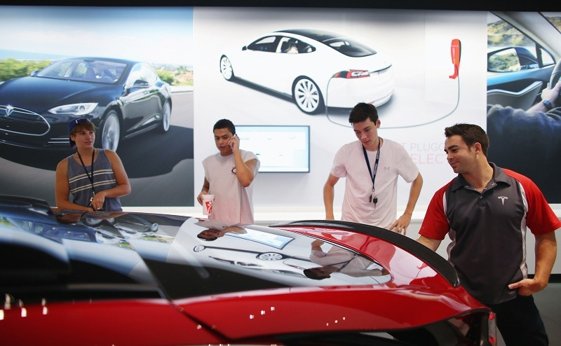Marcelo Jaramillo, assistant store manager, (R) shows a Tesla motor company car in a dealership at the Dadeland Mall on June 6, 2013 in Miami, Florida. The electric car maker is trying to make a move by selling their cars, that can cost between $62,400 and $82,400, into malls and stores.