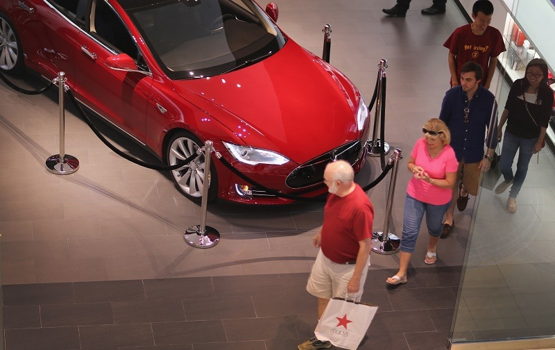 People walk out of a Tesla motor company dealership in the Dadeland Mall on June 6, 2013 in Miami, Florida. The electric car maker is trying to make a move by selling their cars, that can cost between $62,400 and $82,400, into malls and stores.