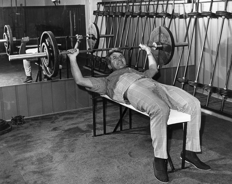 Liberace bodybuilding and building muscle while weight lifting in a gymnasium