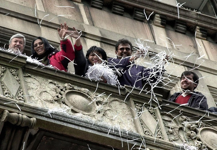 People throw shredded paper (perhaps a resume, built from bad resume templates) from a balcony in New York City