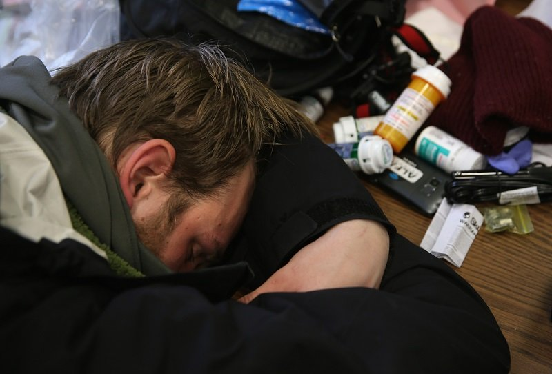 Man resting his head in his arms next to a pile of pill bottles.