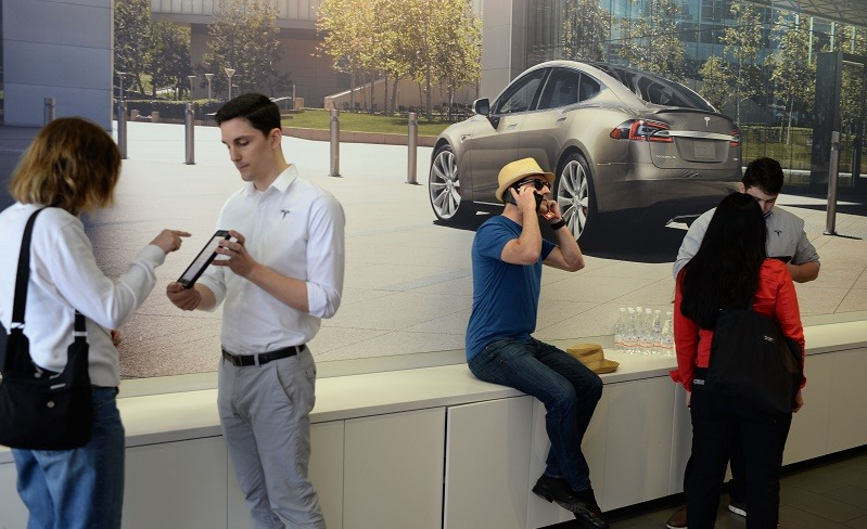 A salesman (2R) help customers pre-order the as yet unseen Tesla Model 3, in the Tesla store on the Third Street Promenade in Santa Monica, California, on March 31, 2016. / AFP / ROBYN BECK (Photo credit should read ROBYN BECK/AFP/Getty Images)