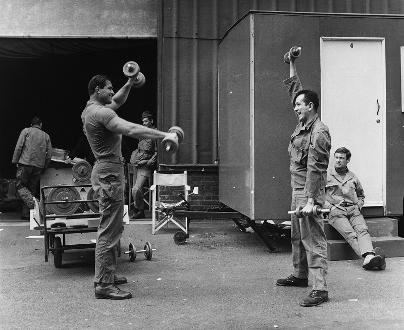 Actors Jim Brown (left) and Trini Lopez, lifting weights and building muscle during the filming of 'The Dirty Dozen'
