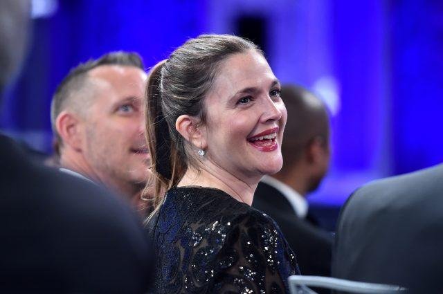 Drew Barrymore smiles while wearing a sparkly gown at an event.