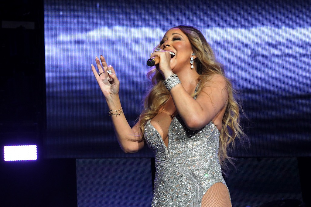 Mariah Carey sings on stage in a glittery leotard