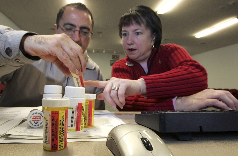 A volunteer helps a man inspect prescription drug information
