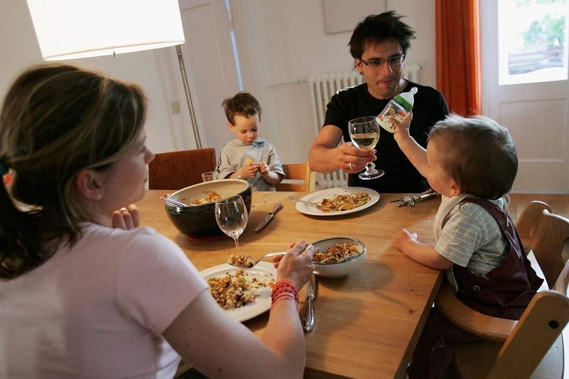 A family eat dinner at home, where it's easier to control your diet