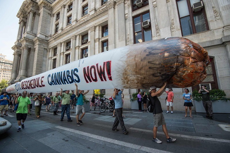 Supporters of marijuana legalization hold a giant inflatable joint during a rally