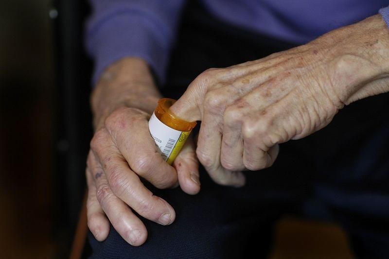 Elderly man reaching into his pill bottle